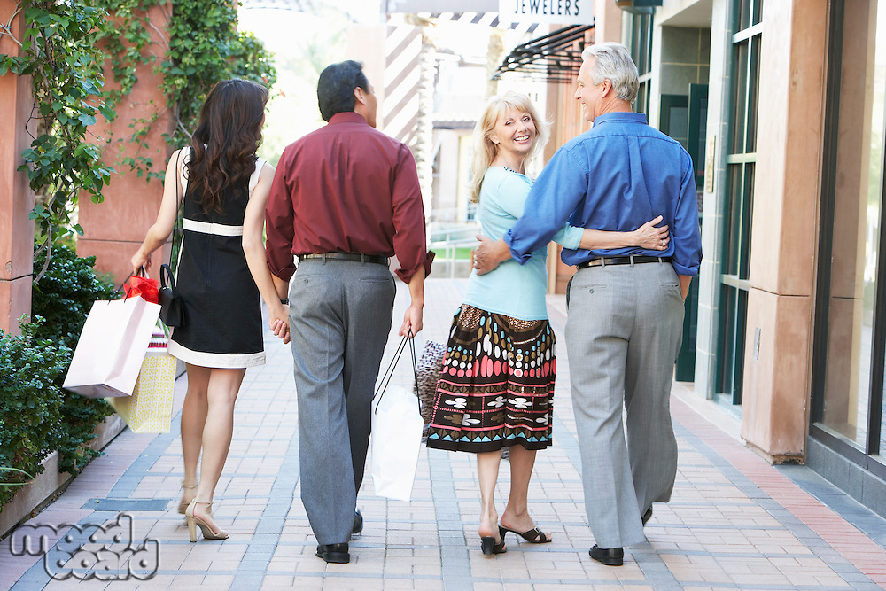 Middle-aged Couples walking holding hands hugging on Shopping Trip back view