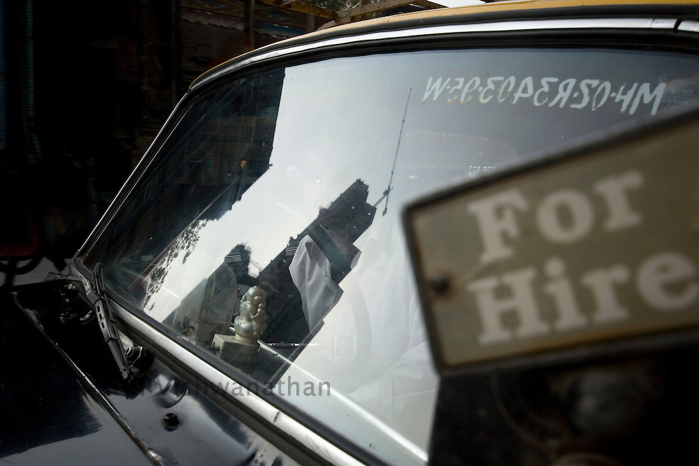 A highrise building under construction is reflected on a taxi cab, in Mumbai, India, on Monday, December 17, 2007. Photographer:  Prashanth Vishwanathan/Bloomberg News