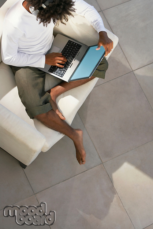 Young man sitting on sofa outside using laptop and listening to music through earphones overhead view