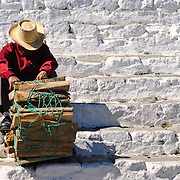 A man selling firewood sits to rest on the steps of Capilla del Calvario, a whitewashed church in the middle of Chichicastengo opposite Santo Tomas Church. Chichicastenango is an indigenous Maya town in the Guatemalan highlands about 90 miles northwest of Guatemala City and at an elevation of nearly 6,500 feet. It is most famous for its markets on Sundays and Thursdays.