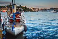 Båt med svensk flagga i skymning vid Strandvägen Nybroviken Stockholm