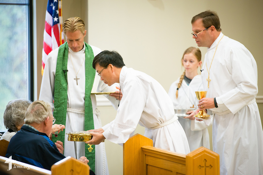 Vicar Yi Sung Chung distributes the Sacrament to an elderly parishioner as the Rev. Tim Droegemueller (left), senior pastor, and Elder Bill Frerking (right) oversee during  Divine Service on Sunday, Nov. 23, 2014, at Living Faith Lutheran Church in Cumming, Ga. LCMS Communications/Erik M. Lunsford