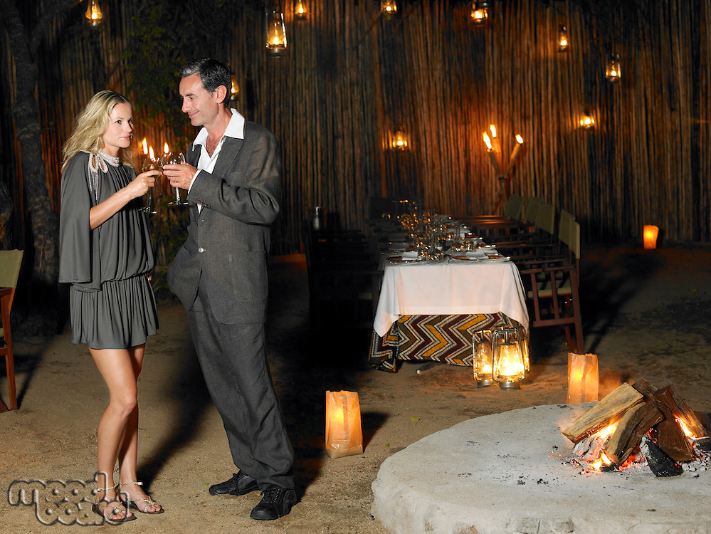 Man and woman toasting at outdoor nightclub near bonfire night