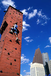 Stock photo of a boy scaling an outdoor rock climbing tower near downtown Houston, Texas