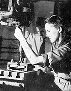 Woman in tank factory being instructed in the use of a metal power drill: 1940. World War II.