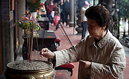 Elderly Taiwanese woman offering incense in a Taipei temple.
