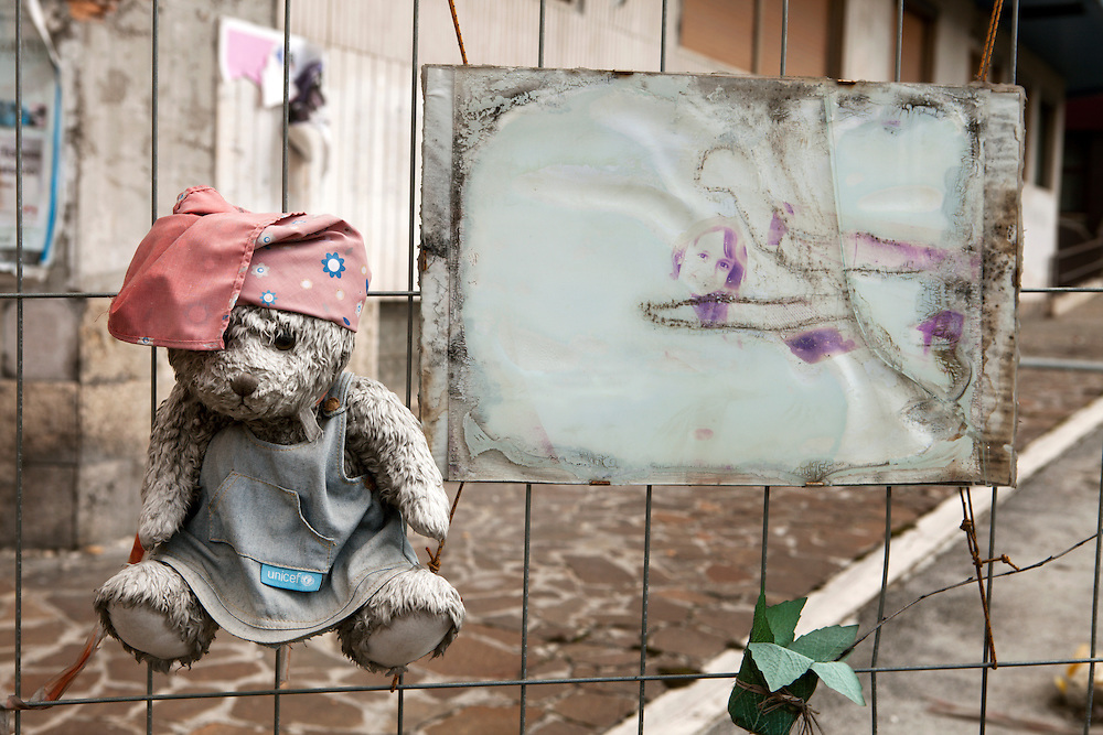A teddy bear put on the enclosure of an unsafe building as tribute of the memory of a young victim of the eartquake. On 6 April 2009 a strong earthquake hit the city of L'Aquila, in the central Abruzzo region of Italy, leaving 308 dead and tens of thousand homeless. 4  years after In the historical center of the city few signs of reconstructions could be seen. On the other hand the effects of the of abandonment add up to the destruction of the quake. .