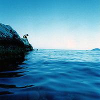 A figure sitting on rocks by a blue sea