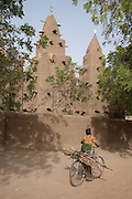 A girl carries firewood on the back of her bicycle past the mud mosque at Barani, northern Burkina Faso.