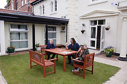 Service Users of Registered Care Home chatting to Support Worker out in the garden,