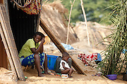 A woman and her child sit outside a makeshift shack where they now live after their home was destroyed by floods in the village of Kpoto, Benin on Wednesday October 27, 2010.