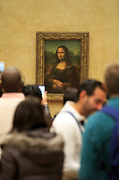 Crowds gather in front of the Mona Lisa by Leonardo DaVinci at The Louvre in Paris, France.