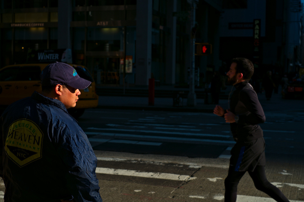 Man waiting to cross street as jogger passes