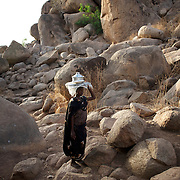 April 28, 2012 - Buram, Nuba Mountains, South Kordofan, Sudan: A Nuba woman passes by carrying a pot of food in the mountains outside Buram village in South Kordofan's Nuba Mountains. Since the 6th of June 2011, the Sudan's Army Forces (SAF) initiated, under direct orders from President Bashir, an attack campaign against civil areas throughout the South Kordofan's province. Hundreds have been killed and many more injured. Local residents, of Nuba origin, have since lived in fear and the majority moved from their homes to caves in the nearby mountains. Others chose to find refuge in South Sudan, driven by the lack of food cause by the agriculture production halt due to the constant bombardments of rural areas.