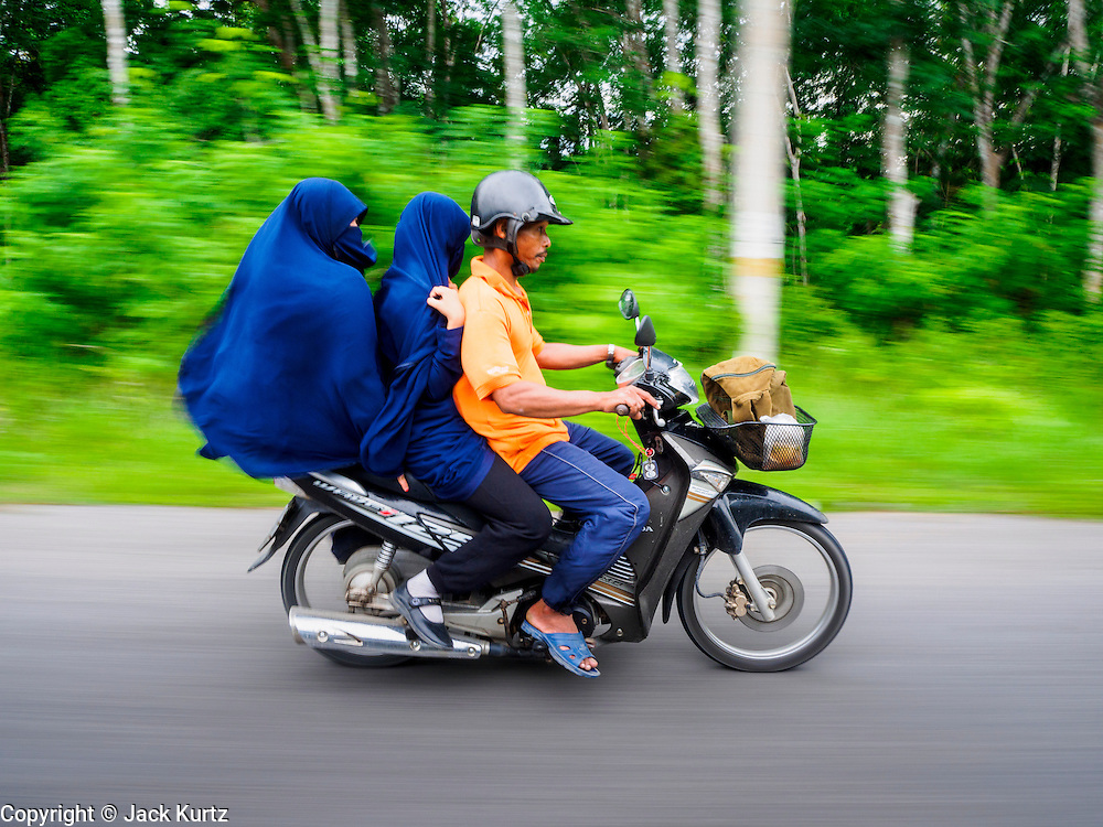 17 JUNE 2015 - PATTANI, THAILAND:    A Thai Muslim family riding a motorcycle in rural Pattani, one of the Thailand's Deep South provinces. PHOTO BY JACK KURTZ