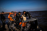 Special Operations battalion (BOPE) soldiers battle the waves to fill their speed boat with with petrol before patrolling along the river shore at the Amazon river mouth in Macapa, Brazil, Wednesday, Oct. 19, 2016. Without a clear role on river patrolling competence several police departments perform insufficient and non coordinated actions of control over the hundreds of canals, unregistered boats and docks that serve as hideaways for river pirates. (Dado Galdieri for The New York Times)