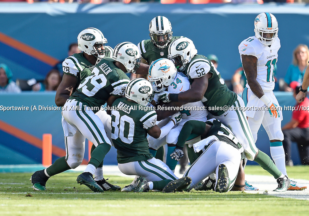 28 December 2014: New York Jets Cornerback Darrin Walls (30) [12314] and Linebacker David Harris (52) [9385] tackle Miami Dolphins Running Back Damien Williams (34) [12525] in the Jet's 37-24 victory at Sun Life Stadium, Miami, Florida.