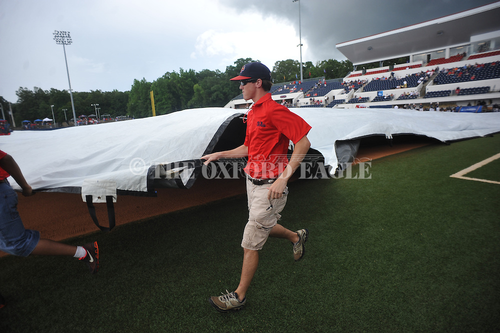Grounds crew member Kellen Weber helps put the tarp on the field during a rain delay before the Georgia Tech vs. Washington at the NCAA Oxford Regional at Oxford-University Stadium on Friday, May 30, 2014. (AP Photo/Oxford Eagle, Bruce Newman)