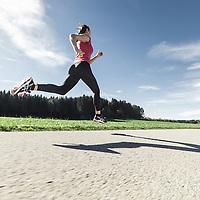 junge Frau läuft auf Landstraße, Münsing, Oberbayern, Deutschland