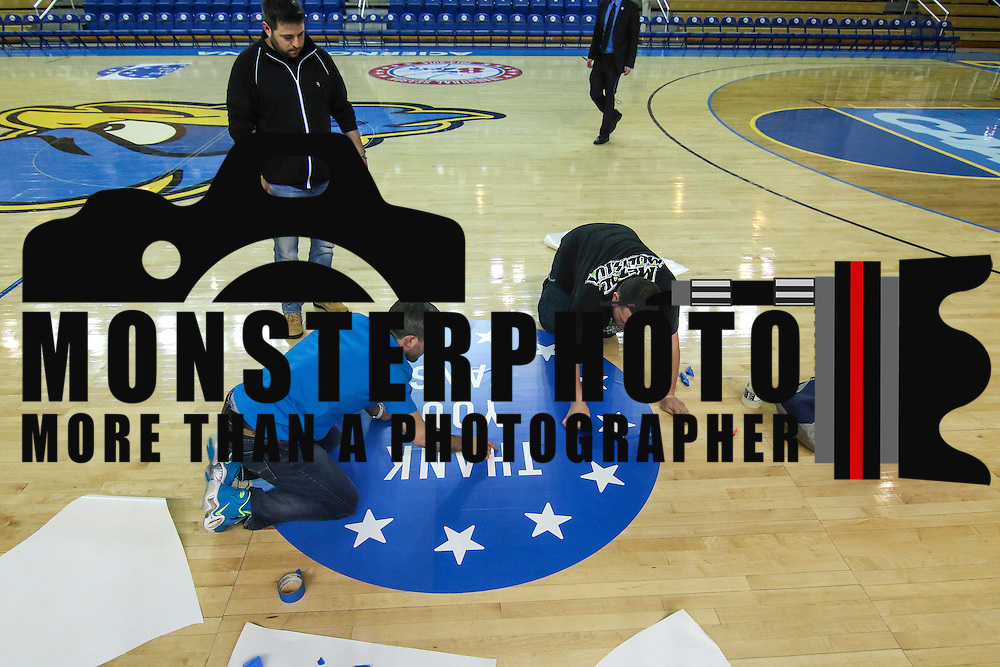 James Personti Jr. ,RIGHT, and Jon Gleber, LEFT, and Jason Gleber, CENTER, of unique Images of Wilmington Delaware place decal on the court in preparation for a Saturday NBA D-league regular season basketball game between the Delaware 87ers (76ers) and Springfield Armor (Brooklyn Nets) Friday, Apr. 04, 2014 at The Bob Carpenter Sports Convocation Center, Newark, DEL.