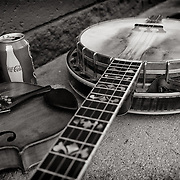 Bluegrass street performers' instruments lay on the ground while the musicians take a rest.