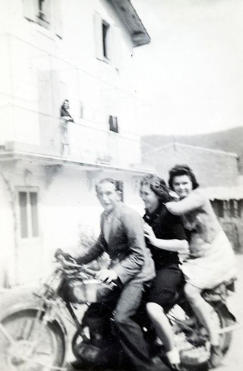 having fun sitting with three people on a motocycle ca 1950s