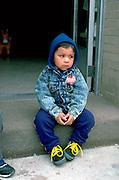 Pensive four year old boy sitting at Cinco de Mayo celebration.  St Paul Minnesota USA