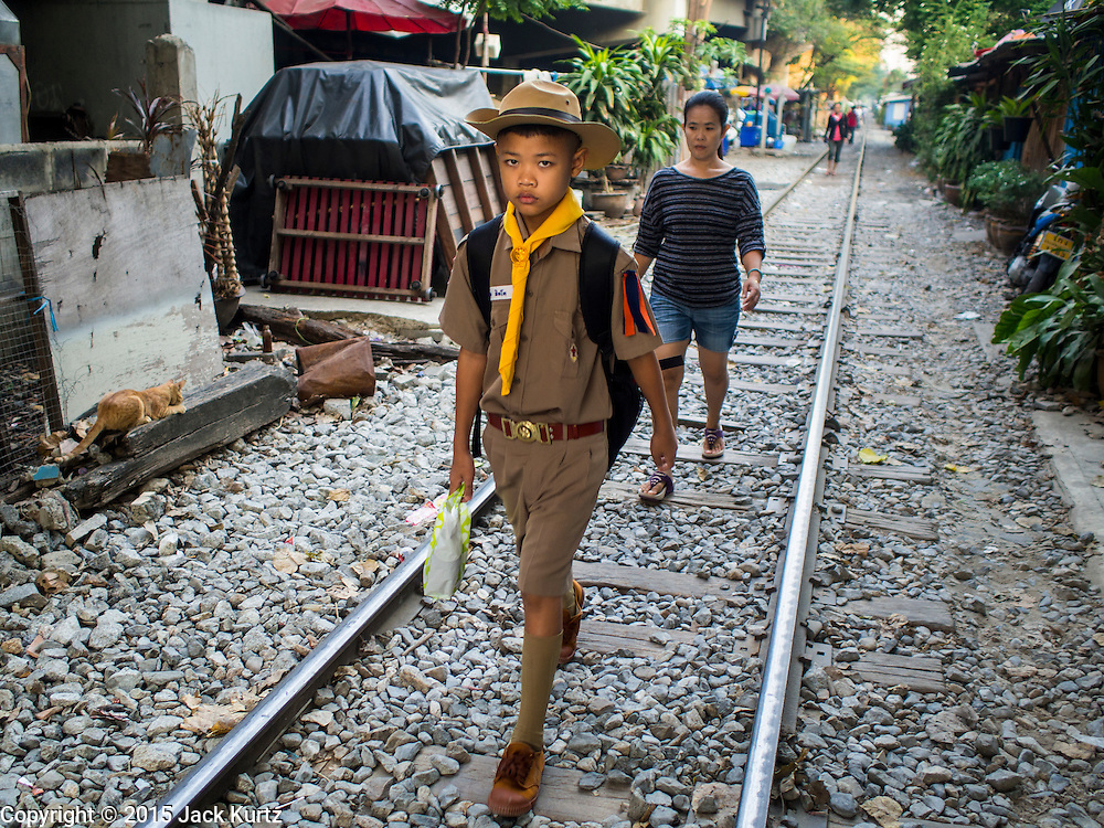 04 FEBRUARY 2015 - BANGKOK, THAILAND: A Thai Boy Scout on his way to school walks along railroad tracks in a working class neighborhood in Bangkok. After months of relative calm following the May 2014 coup, tensions are increasing in Bangkok. The military backed junta has threatened to crack down on anyone who opposes the government. Relations with the United States have deteriorated after Daniel Russel, the US Assistant Secretary of State for Asian and Pacific Affairs, said that normalization of relations between Thailand and the US would depend on the restoration of a credible democratically elected government in Thailand.    PHOTO BY JACK KURTZ