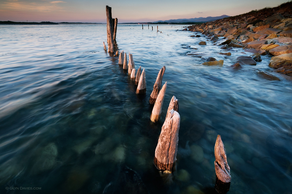 I took this photograph whilst being filmed for a new ITV series &lsquo;The Strait&rsquo; <br /> <br /> The cameraman and I were being bitten senseless by a million midgies as we waited for the tide to rise over these heavily weathered wooden posts. Normally I would have gone exploring whilst waiting for right height for the sea, but the hassle of setting up filming positions meant that perhaps this half an hour was the longest I&rsquo;ve ever waited for a photograph. <br /> <br /> The strong earlier sunshine had weakened behind a soft bank of cloud, removing the high contrast I wanted. However the gentleness of the light has still worked nicely for me nevertheless. Indeed, there is something more calming and serene about the light and colours in this image than originally anticipated.