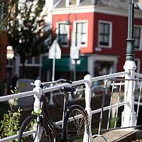 Nederland, Delft , 29 september 2010..Schrijver Kader Abdolah tijdens een wandeling door het centrum van Delft en de Bieslandse Bossen. ..Een fiets aan een brug in oud Delft.