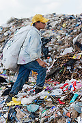 09 NOVEMBER 2004 - TAPACHULA, CHIAPAS, MEXICO: A teenager walks through the municipal garbage dump in Tapachula, Chiapas, Mexico. About 130 people, the poorest of the poor in Tapachula, work in the dump picking through the garbage hoping to find tidbits they can use or sell to brokers who sit on the edge of the dump and resell the garbage. Most of the dump workers are Guatemalan migrants who crossed the border hoping, at one time, to get to the United States. Now they have settled for an existence on the very edge of Mexican society. PHOTO BY JACK KURTZ