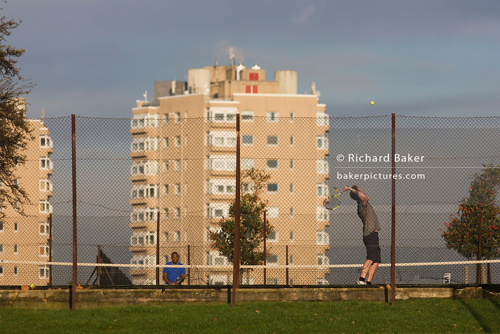 Amateur tennis serve in local court near high-rise flats seen from Brockwell Park, Herne Hill, South London.
