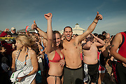 A man and a woman give an entiusiastic thumbs up before entering the water for the annual Pier Swim, heald at the Narragansett Town Beach, on New Year's Day.