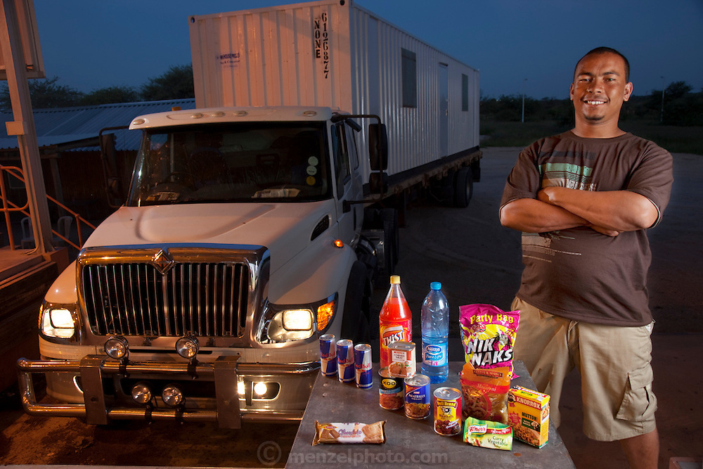 "Tersius ""Teri"" Bezuidenhout, a long-haul trucker delayed by paperwork at the Botswana-Namibia border stands next to his truck with his typical day's worth of road food. (From the book What I Eat: Around the World in 80 Diets.) MODEL RELEASED."