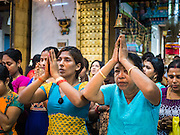 "22 OCTOBER 2015 - YANGON, MYANMAR: Hindus pray in Sri Kali temple in Yangon to honor the goddess Durga on the last day of Navratri. Navratri, literally ""nine nights"" is a Hindu festival devoted to the Goddess Durga. Navratri festival combines ritualistic puja (prayer) and fasting. Navratri in India follows the lunar calendar and is celebrated in September/October as Sharad Navratri. It's widely celebrated in countries in Southeast Asia that have large Hindu communities, including Myanmar (Burma). Many of Myanmar's Hindus are descendants of Indian civil servants and laborers who came to Myanmar when it was the British colony of Burma.  PHOTO BY JACK KURTZ"
