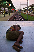 A young homeless boy sleeps on train buffers in the busy Kolkata train station.