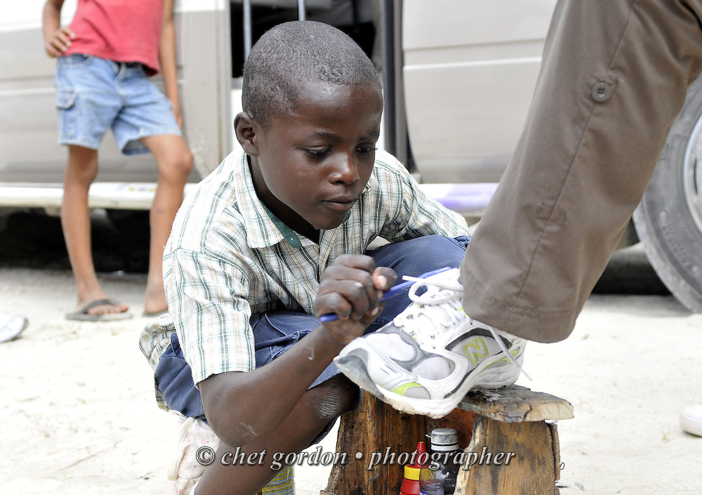 JIMANI, DOMINICAN REPUBLIC.  Young Dominican boy cleans the running shoes of an American doctor in Jimani, Dominican Republic on Tuesday, January 26, 2010.  © Chet Gordon/THE IMAGE WORKS