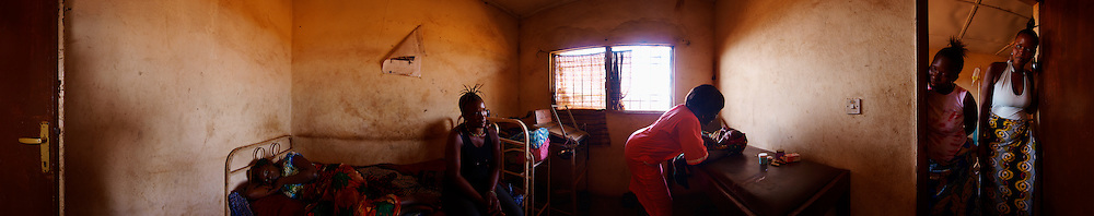 Kadiatu rests in Kroo Bay Health Centre an hour after giving birth to a healthy 3.3 kg baby girl surrounded by her friends and nurse Bintu who helped her deliver the baby, Kroo Bay, Freetown, Sierra Leone.