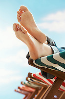 Person resting on deckchair on beach low section close up of feet