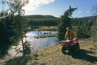 ATV rider looking over river