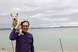 middle aged man with a Jack Russell dog by a lake