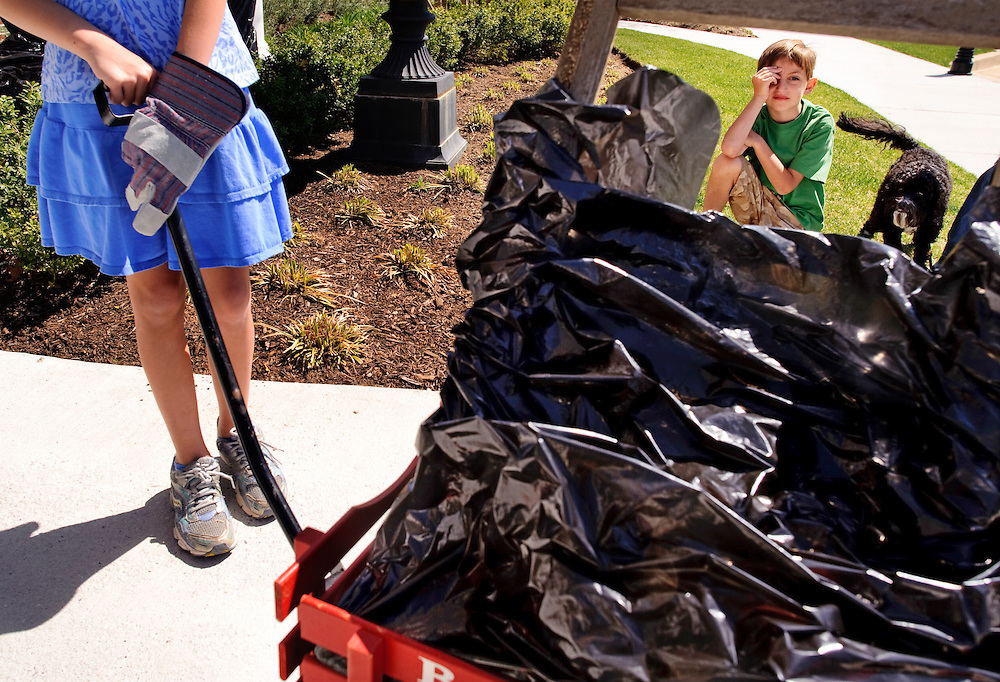 (staff photo by Matt Roth)..Nine-year-old Mia Damiano, left, her brother Michael, 7, Harley, their cockapoo, and mother Ellery Damiano (out of frame) carted the trash they found during Clean Up Fort Meade Day in a red wagon. The family drops off their stash at the Heritage Park Community Center Saturday, April 10, 2010. The event is sponsored by The Enlisted Spouse's Club.