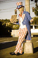 "Uncle Sam on the side of the road holding a ""Out of Gas"" sign."