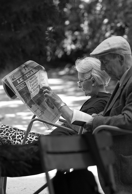 """Black and white photograph of man and wife reading in Paris by Karl R Lilliendahl. This photo is available as Open and Limited Edition Giclee Print in four different sizes. Click on """"Get Print"""" to see more details."""