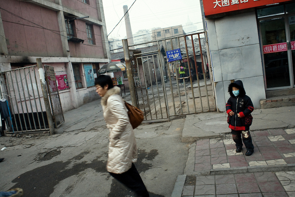 A child wearing a mask against pollution in the streets of Lanzhou, near a chimney of a factory using coal. The pollution is so high that children's respiratory deseases have dramatically increased those last years. <br /> <br /> <br /> -------<br /> Lanzhou, in the Gansu province is one of the most polluted city of China and in the world's top ten for atmospheric pollution due to human activity. The town is situated between two hills along the Yellow River and the polluted clouds remain blocked over the town. The sky is most of the time hidden by the pollution.
