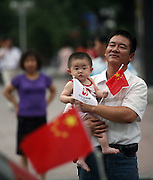 A man carries his granddaughter, carrying flags in advance of the Olympic torch relay in the Wuzhong in Ningxia China.