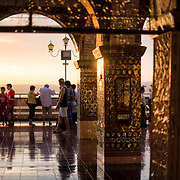 The golden rays of the setting sun catch the gold leaf decorating the portico at Sutaungpyei Pagoda. Sitting on top of Mandalay Hill, Sutaungpyei Pagoda features a large ornately decorate patio that offers scenic views out over the plain on which the city of Mandalay sits.