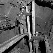 (L-R) Ralph Schmidt and the late Guy Bruneau timbering a staging for drilling a breast in a shrinkage stope, 1300 foot level, Kerr Mine, Virginiatown, Ontario.  (Credit Image: © Louie Palu/ZUMA Press)