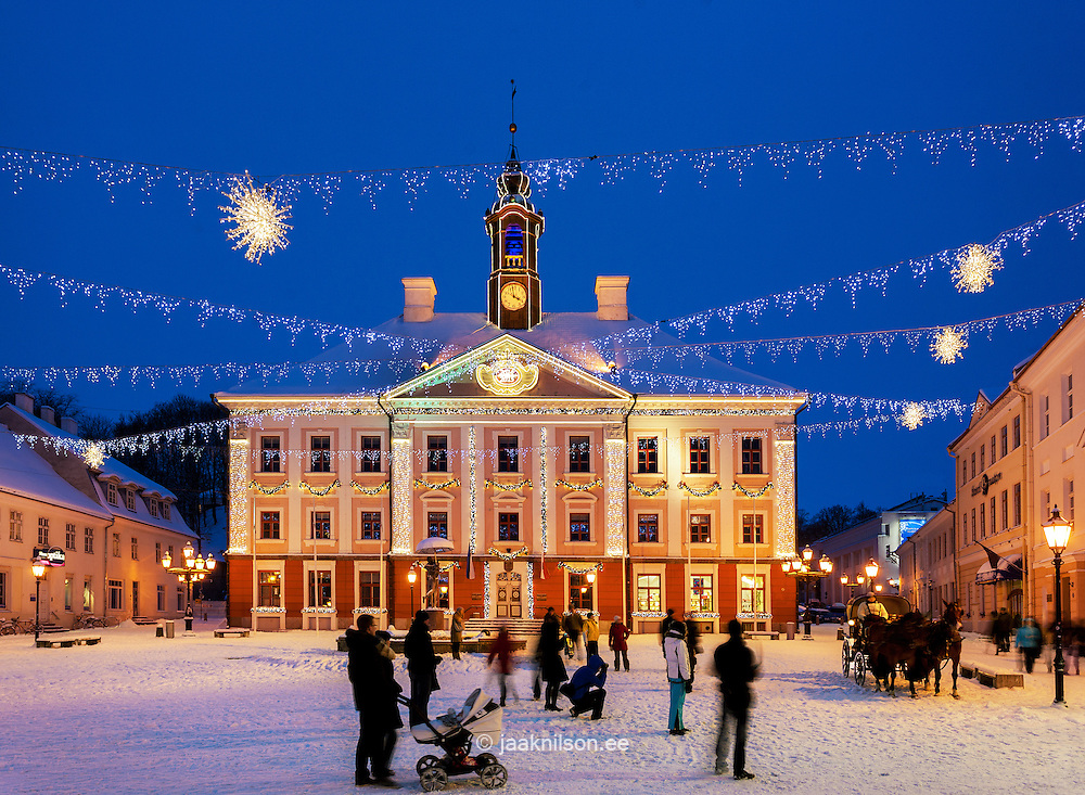 Tartu town hall square in Estonia. Snow covered plaza. Christmas decoration. Lighted building, winter.