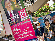 22 JUNE 2011 - BANGKOK, THAILAND: People sit next to a campaign poster in Bangkok, Thailand, Wednesday. Yingluck Shinawatra, leader of the Pheua Thai party is running against  incumbent Prime Minister Abhisit Vejjajiva, head of the Democrat party. Yingluck is the youngest sister of exiled former Prime Minister Thaksin Shinawatra, deposed by a military coup in 2006. Yingluck is currently leading in opinion polls, running well ahead of the Democrat party, which in one form or another has ruled Thailand for most of the last 60 years.   Photo by Jack Kurtz